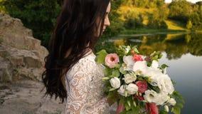 Молодая невеста держа букет на речном береге, конец-вверх сток-видео