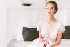 Молодая невеста сидя на кровати дома стоковые изображения rf