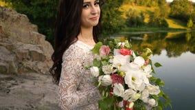 Молодая невеста с букетом в руках смотрит камеру и улыбки, конец-вверх акции видеоматериалы
