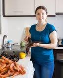 Молодая домохозяйка варя продукт моря Стоковое Изображение