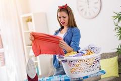 Молодая домохозяйка смотря пятно на одеждах Стоковая Фотография