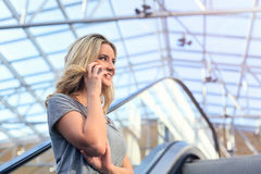 Молодая очаровательная девушка говоря на мобильном телефоне в торговом центре Стоковые Фотографии RF