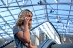 Молодая очаровательная девушка говоря на мобильном телефоне в торговом центре Стоковые Изображения RF