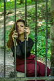 Молодая очаровательная женщина с длинным обидчиком волос, сидит за решеткой в старом каменном пленнике тюрьмы и смотрит pityingly Стоковая Фотография