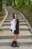 Молодая очаровательная сексуальная девушка с длинными волосами в черном платье гуляет в парке на шагах Стоковая Фотография
