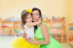 Молодая дочь обнимает мать в шеи Стоковая Фотография