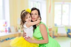 Молодая дочь обнимает мать в шеи Стоковые Изображения