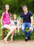 Молодая дочь папы мамы семьи сидя на стенде в парке лета Стоковая Фотография
