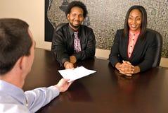 Молодые пары афроамериканца около для подписания бумаг Стоковое фото RF
