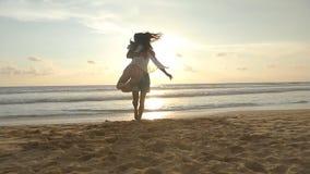 Молодая пара бежит на пляже, объятии человека и закручивает вокруг его женщину на заходе солнца Девушка скачет в ее оружия парня акции видеоматериалы