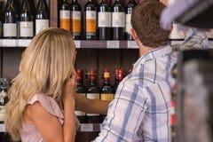 Молодая пара выбирает вино Стоковое Изображение