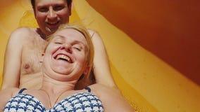 Молодая пара вытягивает водные горки Счастливые праздники совместно в аквапарк сток-видео