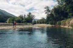 Молодая пара идет вдоль лета реки, совместно вид сзади концепции стоковая фотография