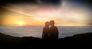 Молодая пара наблюдает морем на заходе солнца Стоковые Изображения