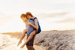 Молодая пара наслаждается средним летом поздно вечером, на влажном san стоковые изображения