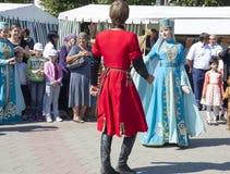 Молодая пара на празднике в костюмах танцуя национальный танец Le Стоковые Фотографии RF