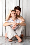 Молодая пара обнимает около белой деревянной стены Стоковая Фотография RF