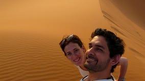 Молодая пара принимая собственную личность изображает пока взбирающся к верхней части большой песчанной дюны в красном море дюны  Стоковые Фото