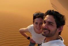 Молодая пара принимая собственную личность изображает пока взбирающся к верхней части большой песчанной дюны в красном море дюны  Стоковые Изображения