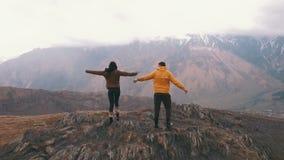 Молодая пара путешественников поднимает его оружия на заднем плане гор акции видеоматериалы