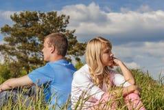 Молодая пара сидит на траве Стоковые Фотографии RF