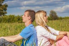 Молодая пара сидит на траве стоковое изображение rf