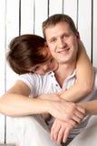 Молодая пара сидит около белой деревянной стены Стоковое Фото