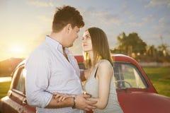 Молодая пара смотря в ` s одина другого наблюдает Романтичные молодые пары сидя на клобуке их автомобиля наслаждаясь моментом Стоковое Фото