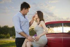 Молодая пара смотря в ` s одина другого наблюдает Романтичные молодые пары сидя на клобуке их автомобиля наслаждаясь моментом Стоковое фото RF