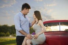 Молодая пара смотря в ` s одина другого наблюдает Романтичные молодые пары сидя на клобуке их автомобиля наслаждаясь моментом Стоковая Фотография RF