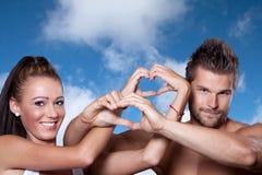 Молодая пара соединяла руки в форме сердца Стоковые Фото
