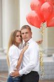Молодая пара с красными воздушными шарами на улице Стоковые Изображения RF