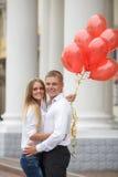 Молодая пара с красными воздушными шарами на улице Стоковое Фото