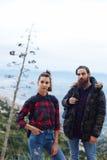 Молодая пара туристов взобранных к верхней части холма и наслаждается красивым видом Стоковое Фото