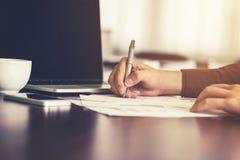 Молодая писчая бумага руки бизнесмена в офисе с sunligh стоковая фотография rf