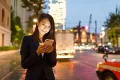 Молодая польза коммерсантки мобильного телефона в городе токио Стоковое Изображение