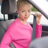 Молодая привлекательная дама прикрепляя ее ремень безопасности стоковое фото