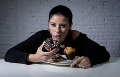 Молодая привлекательная латинская женщина сидя на таблице есть блюдо вполне еды старья слащавой нездоровой Стоковое Изображение RF