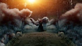Молодая привлекательная ведьма идя на мост в тяжелом черном дыме
