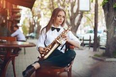 Молодая привлекательная девушка в белой рубашке при саксофон сидя около магазина caffe - внешнего в sity Сексуальная молодая женщ Стоковые Фотографии RF
