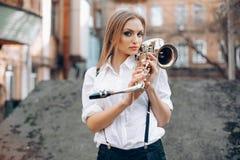 Молодая привлекательная девушка в белой рубашке при саксофон стоя в улице - внешней Сексуальная молодая женщина при саксофон смот Стоковая Фотография RF