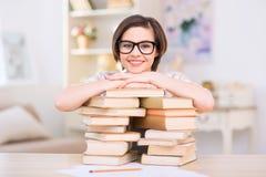 Молодая привлекательная девушка полагается на куче книг стоковая фотография