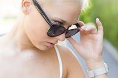 Молодая привлекательная девушка рассматривая ее солнечные очки Стоковая Фотография RF