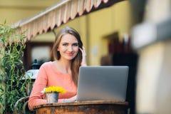 Молодая привлекательная девушка сидя самостоятельно в кофейне Стоковая Фотография RF