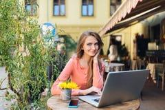 Молодая привлекательная девушка сидя самостоятельно в кофейне Стоковые Фотографии RF