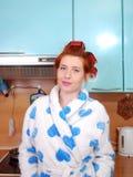 Молодая привлекательная девушка с красными волосами в халате и с обветренными curlers волос стоит в кухне и улыбках Стоковое Изображение