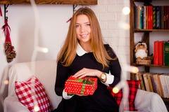 Молодая привлекательная девушка усмехаясь с димплами и держа подарок на празднике Стоковые Изображения