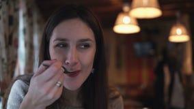Молодая привлекательная женщина брюнет сидя в кафе, разговаривая и есть с ложкой Девушка принимая переговор с кто-нибудь видеоматериал