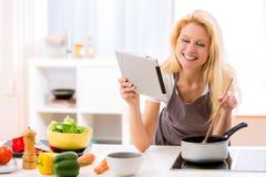Молодая привлекательная женщина варя в кухне Стоковые Фотографии RF