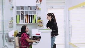 Молодая привлекательная женщина в вскользь носке входит в салон курорта, разговаривает с работник службы рисепшн и радостно идет  видеоматериал